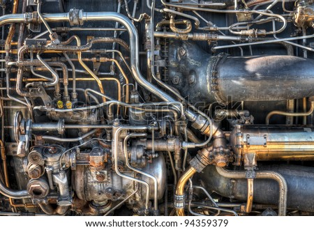 The pipes and mechanical systems of an aircraft jet engine.  Would make a great steam punk background. - stock photo