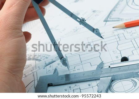 The plan industrial details and a hand with divider. A photo closeup. Blue toning - stock photo