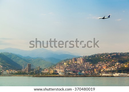 The plane flying on landing about the coastline at the Black Sea - stock photo