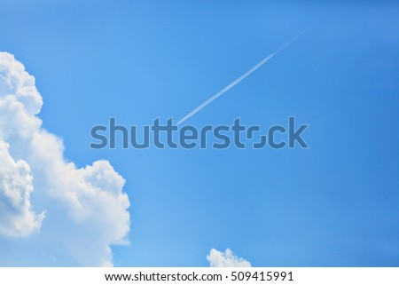 The plane is flying in the sky with clouds