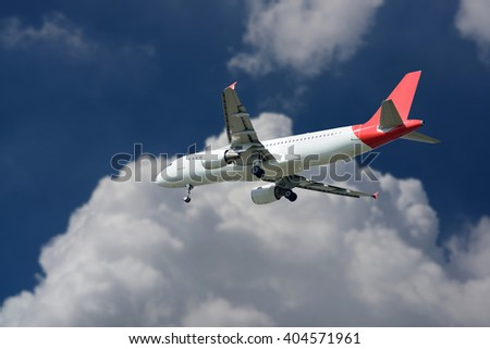 The plane was landing on sky-clouds background.