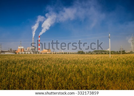 The plant with smoking chimney in the background field of rye. - stock photo