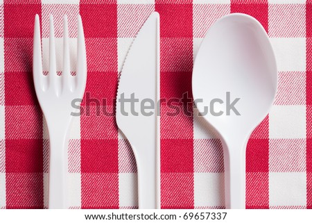 the plastic cutlery on checkered tablecloth - stock photo
