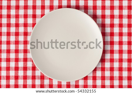 the plate on checkered table cloth - stock photo