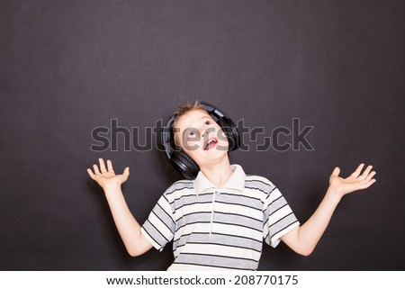 The playful boy  listening to music in headphones - stock photo