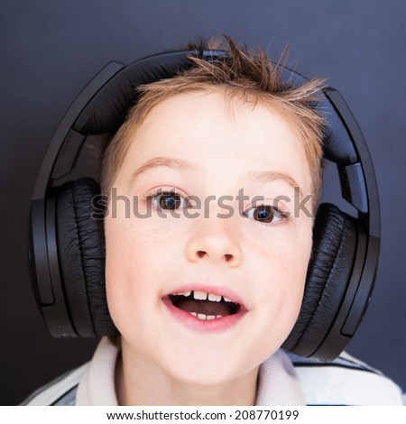 The playful boy  listening to music in headphones