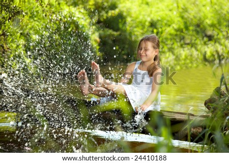 The playful girl sprays feet pond water