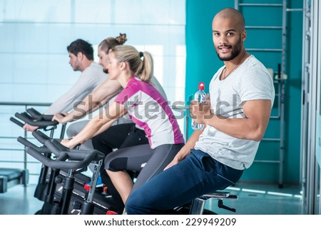 The pleasure of training. Young boy smiling at the camera and sitting on the bike and holding a bottle of water while his three friends pedal in the gym - stock photo