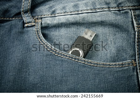 The pocket of jeans with flash card. Cloth background. Toned. - stock photo