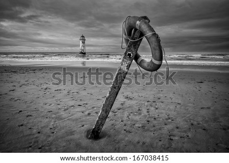 The �Point of Ayr� lighthouse on Talacre Beach  Wales with footpath sign and life ring in black and white. - stock photo