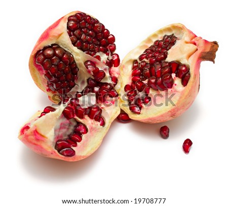 The pomegranate divided into parts. The juicy fruit containing set of vitamins, useful to a human body. Isolation on white.