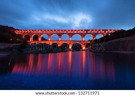 The Pont du Gard (Bridge of the Gard) is an ancient Roman aqueduct bridge that crosses the Gardon River in Vers-Pont-du-Gard near Remoulins, in the Gard d���©partement of southern France, Europe. - stock photo