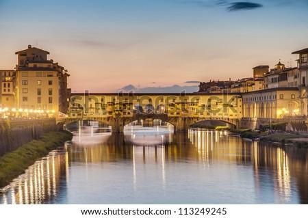The Ponte Vecchio (Old Bridge), a Medieval stone closed-spandrel segmental arch bridge over the Arno River in Florence, Italy. - stock photo