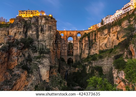 The popular historic landmark of spectacular Puente Nuevo, New Bridge, at dusk over Guadalevin River in town of Ronda, Andalusia, Spain. - stock photo