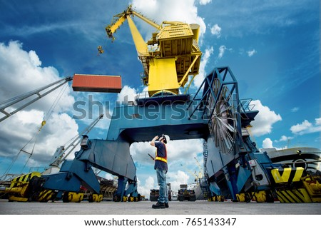 the port industrial gantry crane working under command of the loading master for loading and discharging unit of containers from storage yard to the ship alongside berthing in the terminal