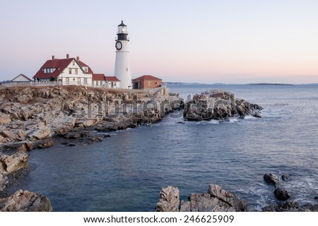 The Portland Head Lighthouse on Cape Elizabeth moments before Sunrise lights up the rocks and the lighthouse - stock photo