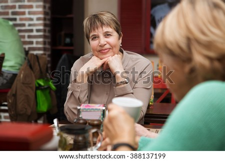 the portrait laughing of senior woman in smart clothes having tea in cafe with girlfriends