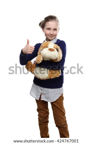 the portrait of a adorable  little teenage girl with a toy in one hand and other hand shows gesture thumbs up isolated on white  isolated on white background - stock photo