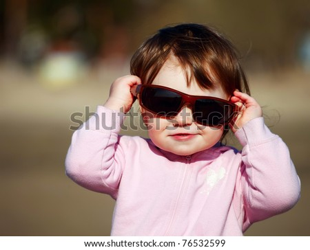 The portrait of a little girl in sunglasses