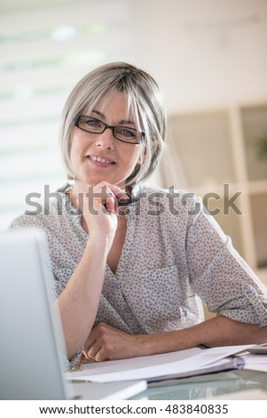 the portrait of a pretty senior  woman  with gray hairs who wears glasses and who works at home with a laptop. she is studying english lessons . this is a hobby