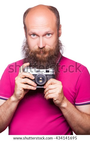 The portrait of bald bearded man photographer with pink t shirt holding classic camera. isolated on white background. studio shot.  - stock photo