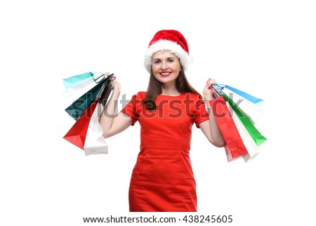 the portrait of beautiful smiling young adult girl wearing on red dress and red Santa Claus hat holding a colors shopping bags in her arms isolated on white background - stock photo