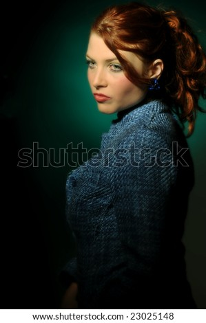 The portrait of redhead attractive young woman in blue coat.