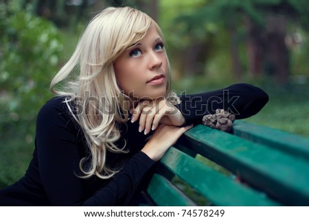 The portrait of the beautiful girl sits on a bench in green park - stock photo