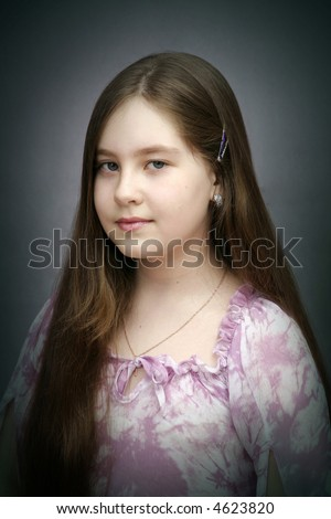 The Portrait of the girl-teenager in pink blouse on gray background. - stock photo