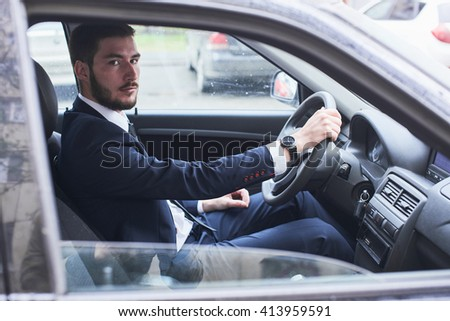 The portrait of the guy in the suit sitting behind the wheel of a car
