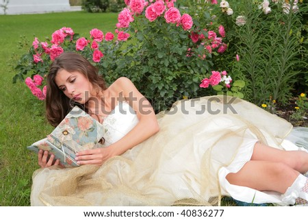 the portrait of the princess with book in hand in the flowers - stock photo
