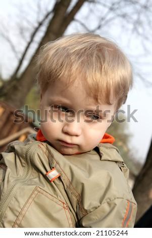 The portrait of the sad boy outdoor - stock photo