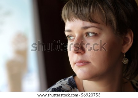 The portrait of thoughtful woman at home - stock photo