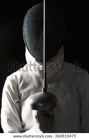 The portrait of woman wearing white fencing costume  on black  - stock photo
