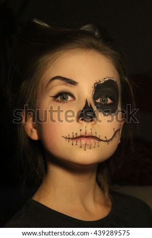 the portrait of young little beautiful girl with skull makeup on black background  - stock photo