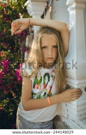 The portrait young girl about 9-12 years old with the blonde and loose hair that stands near the columns with the purple flowers in the rays of the setting sun. She wears top-shirt and shorts.
