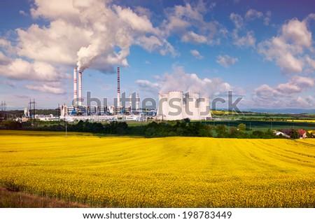 the power station Pocerada with rape field, toned image - stock photo