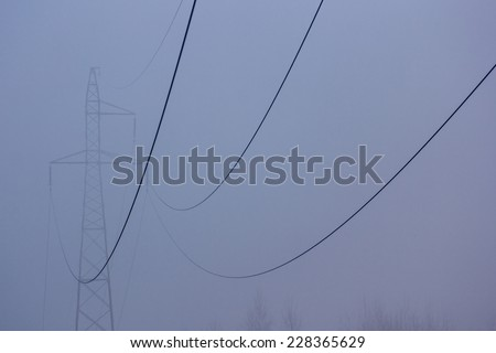 The powerlines in the foggy mistic morning - stock photo