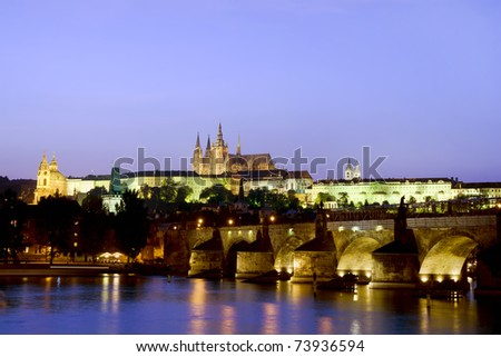 The Prague Castle and the Charles Bridge at dusk in Prague, Czech Republic, Vltava river in foreground - stock photo