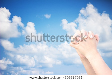 The praying hands on a sky background. - stock photo