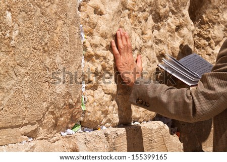 The praying with a book in his hand leaning against the Wailing Wall - stock photo
