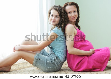 The pregnant woman and her young sister - stock photo