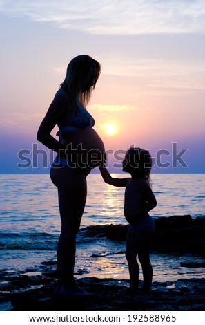 The pregnant woman and the small child (against the sea). - stock photo