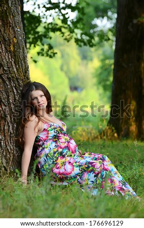 The pregnant woman in summer on grass - stock photo