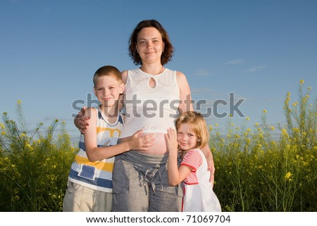 The pregnant woman with children to the nature.
