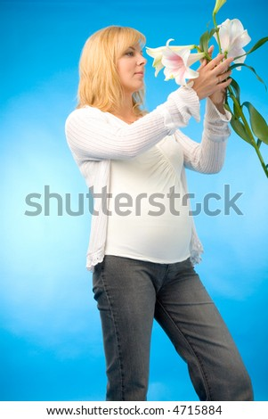 the pregnant woman with madonna lily on blue background