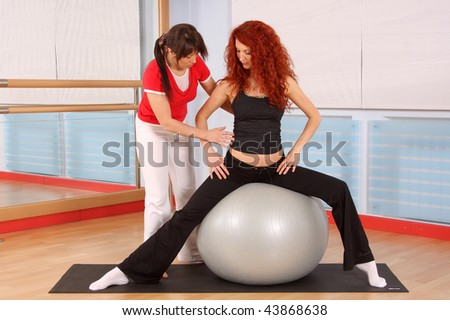 The pregnant woman with the instructor is engaged in gymnastics in a sports hall