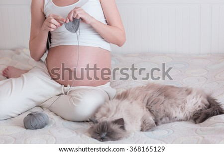 the pregnant young woman knits in a bedroom