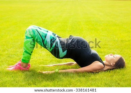 The pregnant young woman plays sports on a grass - stock photo