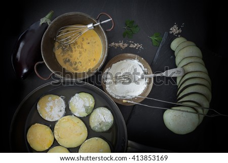 The preparation of fried eggplants necessary to prepare the Italian traditional recipe, parmigiana. Raw slices dipped in egg and flour and put to fry in olive oil. - stock photo